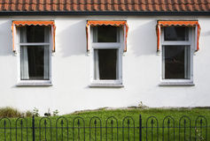 Three windows. With orange awnings, a small garden and roof tiles. A typical dutch house Stock Photo