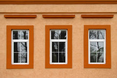 Three windows on the orange  wall Stock Photo