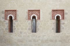 Three windows in a row. Three front glass small windows of an old medieval house royalty free stock photos