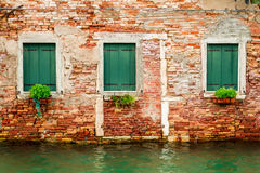 Three windows in ruined house on a canal in Venice stock photos