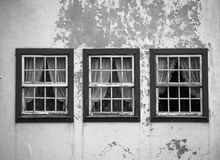 Three windows on the shabby wall closed with curtains Royalty Free Stock Photo