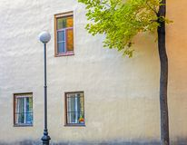 Three windows on the wall of the house, a street lamp and a tree royalty free stock images