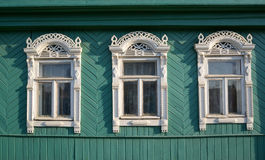 Three windows with white carved platbands Stock Image