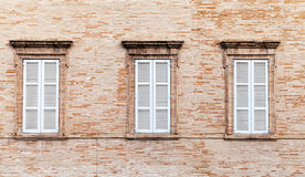 Three windows with white closed wooden shutters royalty free stock images