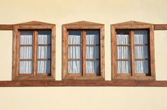 Three Windows. Of wood on a yellow facade Stock Photography