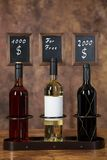 Three wIne bottles with a price board Royalty Free Stock Images