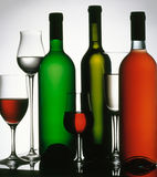 Three wine bottles and several glasses. Stock Photography
