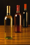 Three wine bottles on wooden table and black background Royalty Free Stock Photography