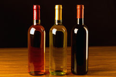 Three wine bottles on wooden table and black background Royalty Free Stock Photos