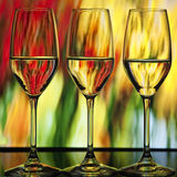 Three wine glasses. Three beatiful wine glasses with orange, green and yellow lighted background which looks like fire Royalty Free Stock Images