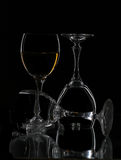 Three wine glasses. Macro view of three wine glasses in different positions reflecting on black background Stock Photo