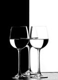 Three wine glasses. In backlight on the black and white contrast background Royalty Free Stock Images