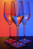 Three wine glasses with colored background Stock Images