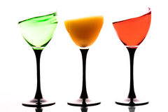 Three wine glasses with colored liquids on a white background. Three wine glasses with colored liquids in motions on a white background Royalty Free Stock Photo