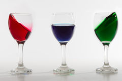 Three wine glasses with colour water spill on white background w Royalty Free Stock Photo