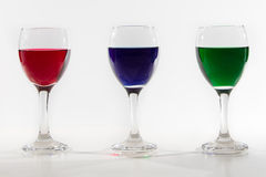 Three wine glasses with colour water spill on white background w Royalty Free Stock Images
