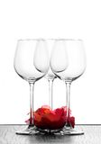 Three wine glasses and flower. Three wine glasses in backlight with red flower Royalty Free Stock Photo