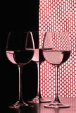 Three wine glasses over grid. Three wine glasses in backlight on the black and white contrast background over red grid Stock Images