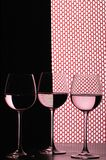 Three wine glasses over grid. Three wine glasses in backlight on the black and white contrast background with red grid fish net Royalty Free Stock Image