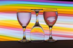 Three wine glasses in a row with a rainbow of color behind them stock images