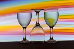 Three wine glasses in a row with a rainbow of color behind them royalty free stock photo