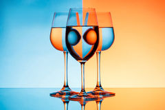 Three wineglasses with water over blue and orange background. Stock Photography