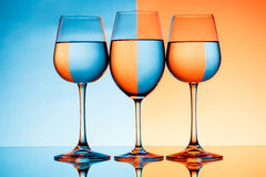 Three wineglasses with water over blue and orange background. Royalty Free Stock Image