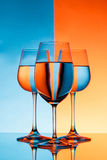 Three wineglasses with water over blue and orange background. Stock Photo