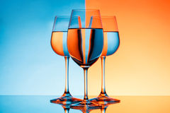 Three wineglasses with water over blue and orange background. Royalty Free Stock Photo