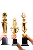 Three winners. Holding the trophies against white background stock photo