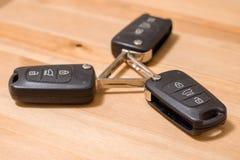 Three wireless car keys on wooden background royalty free stock photos