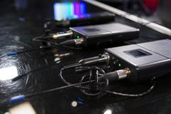 Three wireless microphone transmitter and three wireless microphone reciever on black table in tv studio stock photography