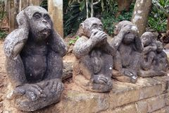 Three wise monkeys stone figurines stock photography