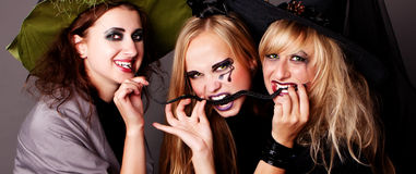 Three witches eat thin black snake. Halloween Stock Images