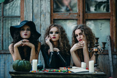 Three witches at the table Stock Image