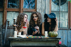 Three witches at the table. Three witches are sitting at the table and prepared the potion on the eve of Halloween Royalty Free Stock Photography