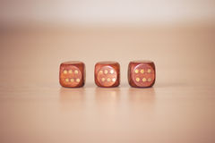 Three woden dices on light beige table Stock Image