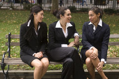 Three woman on bench. Three young multi-ethnic woman sit and talk on a park bench in the city stock image