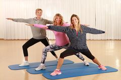 Three woman of different ages doing stretching and power work outs stock photography