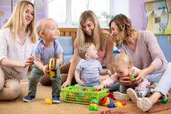 Three woman friends with toddlers playing on the floor in sitting room. Three women friends with kids toddlers having a fun sitting on the floor in playroom royalty free stock photography