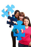 Three woman showing big jigsaw Royalty Free Stock Photography
