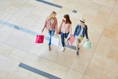 Three women as friends in shopping mall. Group of young women as friends with shopping bags in shopping mall stock image