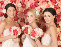 Three women with background full of roses Royalty Free Stock Photos