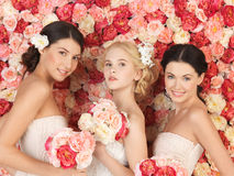 Three women with background full of roses Stock Photography