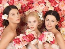 Three women with background full of roses Stock Image