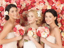 Three women with background full of roses Stock Photos