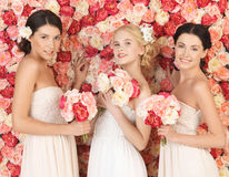 Three women with background full of roses Stock Photo