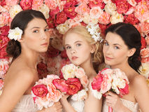 Three women with background full of roses Royalty Free Stock Images