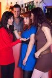 Three women in a bar talking. Royalty Free Stock Photos