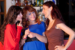 Three women in a bar talking. Three women in a bar sharing stories, bottles of liquor seen in the background Royalty Free Stock Photos